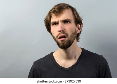 Closeup portrait speechless, insulted shocked, stunned surprised young man, in disbelief isolated grey background. Negative human emotion, facial expression, bad feelings, body language, panic attack