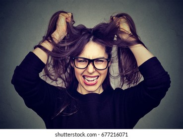 Closeup portrait stressed angry woman pulling hair out screaming