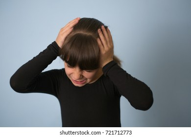 Closeup portrait stressed child, teenager girl hands on temples overwhelmed at school in life, isolated grey wall background. Human facial expressions, emotions, feeling, perception
