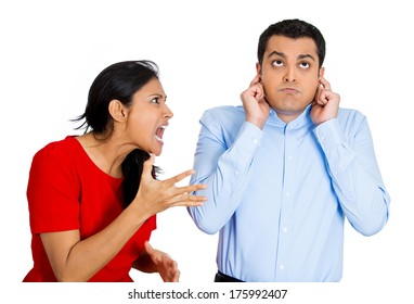 Closeup portrait of stressed couple going through hard times in relationship, isolated on white background . Young woman yelling screaming shouting at man, he is annoyed and ignores closes plugs ears.