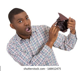 Closeup portrait of stressed, upset, sad, unhappy young man standing with, showing you empty wallet, isolated against white background. Financial difficulties, bad economy concept. Negative emotion