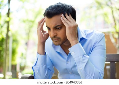 Closeup portrait, stressed young business man, hands on head with bad headache, isolated background of trees outside. Negative human emotion facial expression feelings.