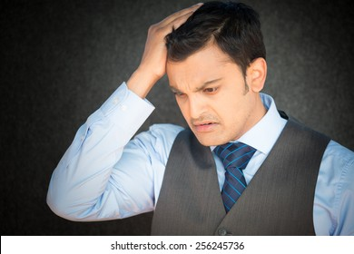 Closeup portrait, stressed young business man with vest and tie, hand on head with bad headache, isolated gray black. Negative human emotion facial expression feelings.