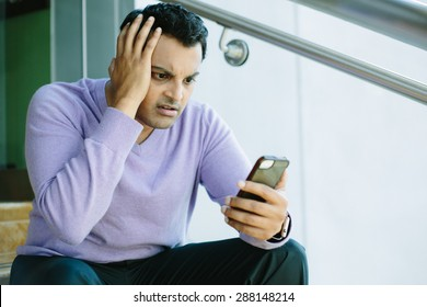 Closeup portrait, stressed young man in purple sweater, shocked surprised, horrified disturbed, by what he sees on his cell phone, isolated indoors background.