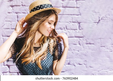 Close-up portrait of stunning blonde girl with hair waving posing with eyes closed and cute smile. Aorable young woman in straw hat enjoying summer wind while spending time outside.