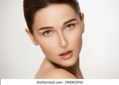 close-up portrait of stunning female with perfect skin and glossy lips looking to camera with her brown eyes