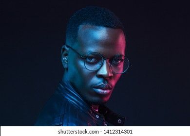 Close-up portrait of stylish black man, wearing leather jacket and hipster round glasses