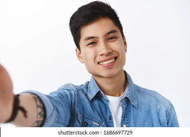 Close-up portrait of stylish handsome asian man with earring, denim jacket, taking selfie on smartphone, video-calling friends via app, smiling pleased, white background