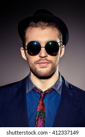 Close-up portrait of a stylish young man wearing black round sunglasses. Optics style. Fashion studio shot.