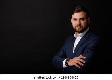 Close-up portrait of a successful businessman in a suit on a black background. The concept of a leadership.