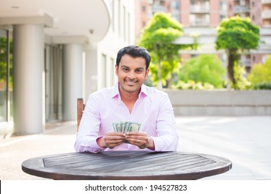 Closeup portrait, super happy excited successful young business man holding money dollar bills in hand, isolated background of trees, building. Financial reward