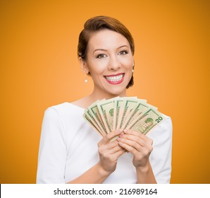 Closeup portrait super happy excited successful young business woman holding money dollar bills in hand, isolated orange background. Positive emotion facial expression feeling. Financial reward