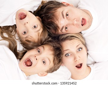 Close-up portrait of a surprised family having fun together lying on a bed at home - top view