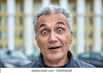 Closeup portrait of a surprised man with short gray hair and over 50 years. Middle-aged male with pop-eyed in the outdoors. Astonishment in the eyes of businessman or official near government building