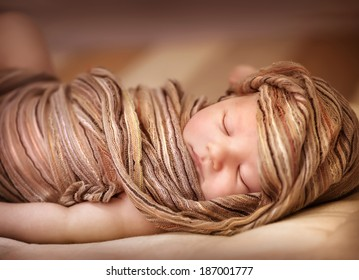 Closeup portrait of sweet baby girl asleep covered with fashionable beige shawl, little child relaxing at home, day dream, peace and carefree concept