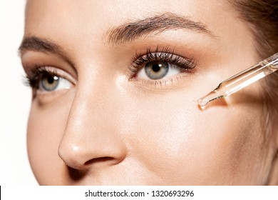 Close-up portrait of sweet girl with shiny skin applying drop of face oil. Beauty treatment and wellness concept. Cute model using modern cosmetology on white background