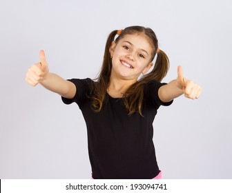 Closeup portrait sweet little, happy, smiling, relaxed excited girl giving thumbs up, isolated  grey background. Childhood, positive emotion, facial expressions, reaction, attitude, life perception