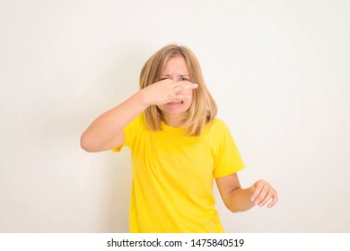 Closeup portrait of teen girl pinches nose with fingers hands looks with disgust something stinks, bad smell isolated with copyspace. Human face expression body language reaction