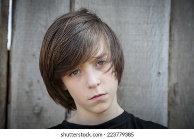 closeup portrait of a teenage boy in front of a wood background