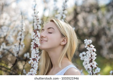 Closeup portrait of teenage girl inhales aroma of flowering apricot trees in the garden