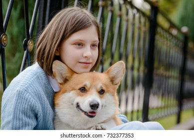 Close-up portrait of a teenage girl and a welsh corgi pembroke