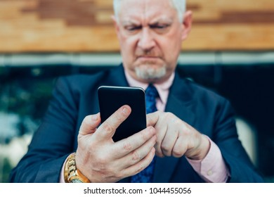 Closeup portrait of tensed senior handsome man using smartphone outdoors with focus on smartphone and hands. Front view.