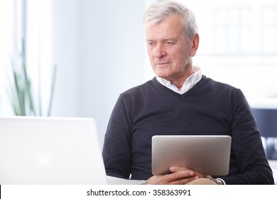 Close-up portrait of thinking old businessman working on laptop and holding in his hand a digital tablet while sitting at office.