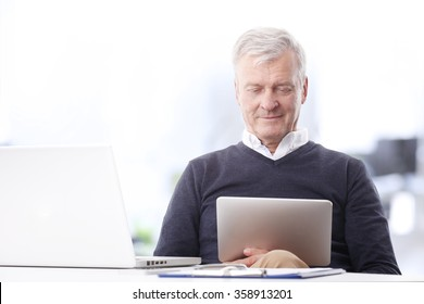 Close-up portrait of thinking old businessman working on digital tablet while sitting at office in front of laptop.