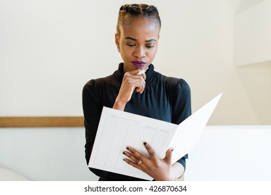 Close-up portrait of thinking successful African or black American business woman holding a big white file and pen near chin