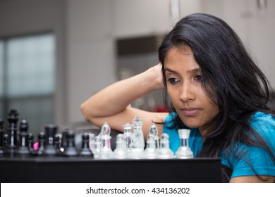 Closeup portrait, thinking woman in blue shirt playing chess, wondering next move, isolated indoors background