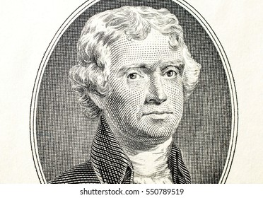 Closeup of the portrait of Thomas Jefferson on the front of a two dollar bill.