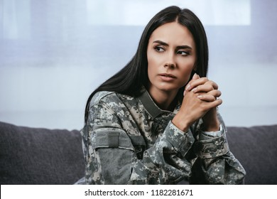 close-up portrait of thoughtful female soldier in military uniform with ptsd sitting on couch and looking away