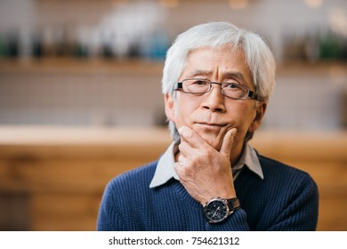 close-up portrait of of thoughtful senior asian man