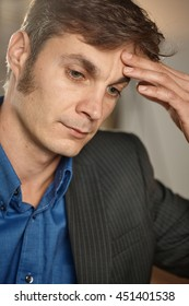 Closeup portrait of thoughtful troubled businessman thinking, hand on forehead, looking down.