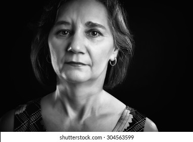 Close-up portrait of a thoughtful woman, middle aged, looking at the camera, isolated on black. Black & white picture.
