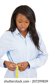 Closeup portrait thoughtful, young attractive woman measuring her waist with measuring tape, isolated white background. Weight loss, control program concept. Healthy life style, body care, exercise