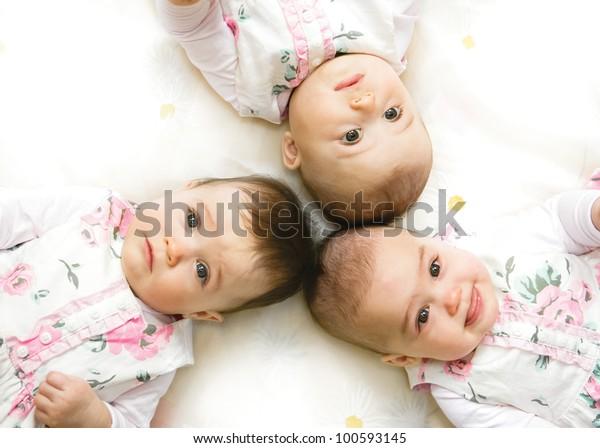 Close-up portrait of three babies lying on floor