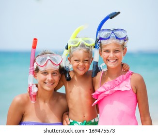 Closeup portrait of three happy children on beach with colorful face masks and snorkels, sea in background.