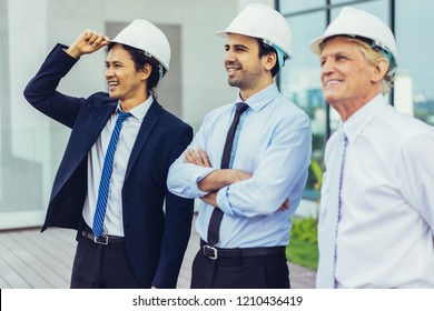 Closeup portrait of three smiling diverse business people looking away, wearing helmets and standing outdoors with building in background. Developers concept.