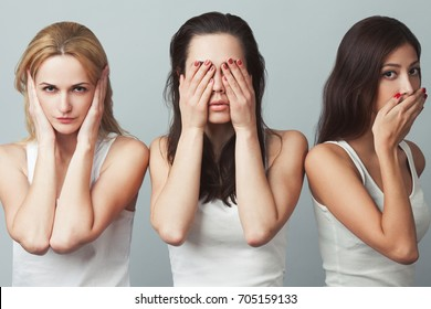 Close-up portrait of three young women in white sleeveless shirts imitating see no evil, hear no evil, speak no evil concept on gray background. Human emotions, expressions, communication. Studio shot