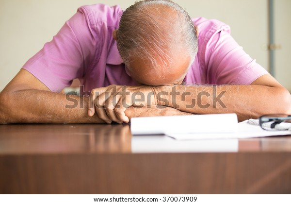 Closeup portrait, tired old bald boss sleeping after filling out so much paperwork, resting on desk, isolated indoors background. Grueling work hours, need more caffeine
