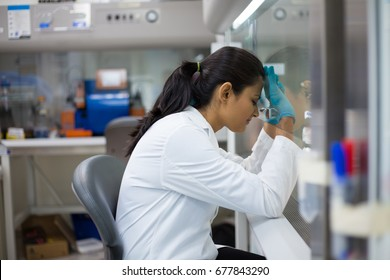 Closeup portrait, tired young woman scientist,crashing, with failed experiments and working long hours, leaning head against glass fume hood with mirror reflection. Isolated laboratory