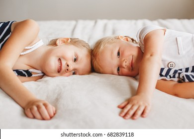 Closeup portrait of two cute adorable little red-haired blonde Caucasian girls sisters lying together on bed at home. Siblings hugging looking in camera. Happy lifestyle childhood concept.