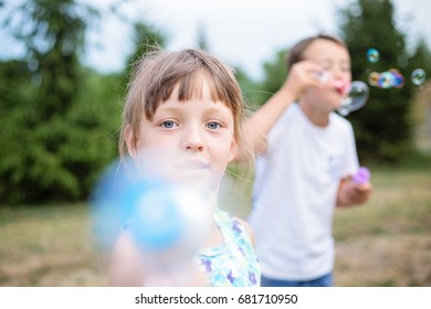 Close-up portrait of two eastern european small children blowing bubbles outdoors in park on summer day