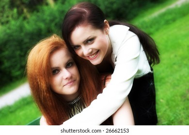 Close-up portrait of two girl-friends during their walk in a park