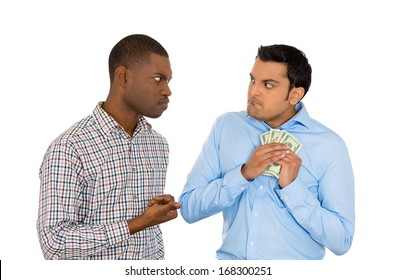 Closeup portrait of two men, one trying to steal money from the other, who is tightly holding cash and not willing to give it up. Street crime, violence. Negative human emotions, conflict resolution
