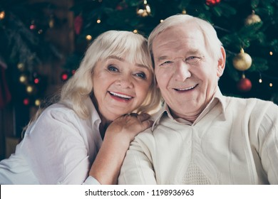 Closeup portrait of two nice cheerful positive adorable beautiful grey-haired married spouses granny grandpa wife cuddling husband having fun near decorated fir tree in house
