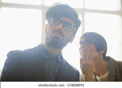 Closeup portrait of two office workers gossiping about newcomer: young woman leaning in to whisper in colleagues ear as they both looking judgingly at someone