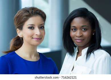 Closeup portrait, two office workers standing together united in their workplace, isolated indoors inside background. Positive emotions