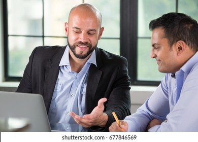 Closeup portrait of two people having business discussion on laptop, isolated indoors office window background